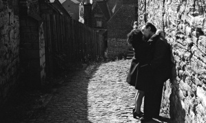 A middle-aged couple kiss in a back alley in Durham.