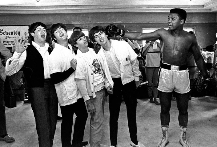 FILE - In this Feb. 18, 1964, file photo, The Beatles, from left, Paul McCartney, John Lennon, Ringo Starr, and George Harrison, take a fake blow from Cassius Clay, who later changed his name to Muhammad Ali,  while visiting the heavyweight contender at his training camp in Miami Beach, Fla. Ali turns 70 on Jan. 17, 2012. (AP Photo/File)