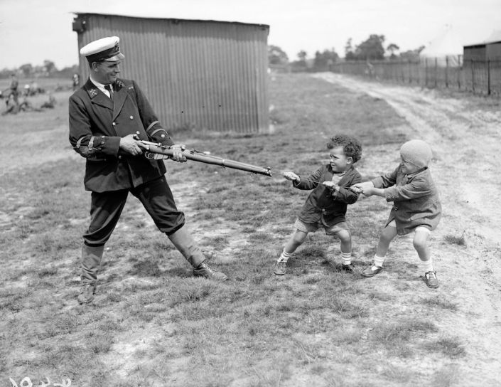 June 1927:  Two little boys playing tug of war with a uniformed competitor and his gun during a break in the competition at Bisley rifle range !  (Photo by Fox Photos/Getty Images)